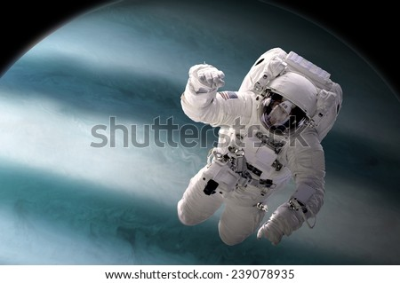A depiction of an astronaut floating in outer space. A large, Jupiter-like planet sees composes the background. Elements of this Image Furnished by NASA. - stock photo