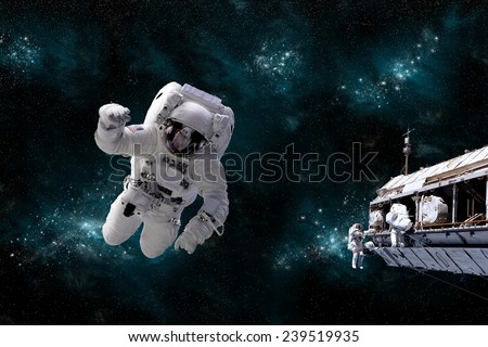 A depiction of an astronaut floating in outer space while his fellow astronauts work on the space station.  A galactic scene serves as background. Elements of this Image Furnished by NASA. - stock photo