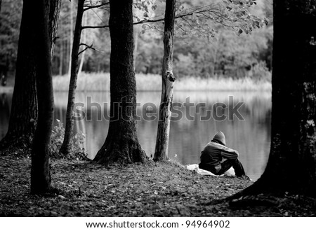 A depressed, lonely person wearing a hood is sitting near the lake - stock photo