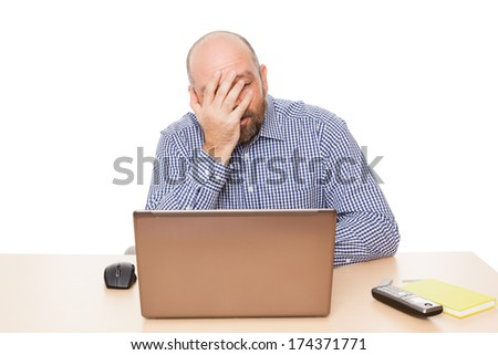 A depressed man in front of a notebook computer, isolated on white background. - stock photo