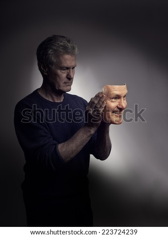 A depressed man putting on a mask of his own, happy, smiling face, - stock photo