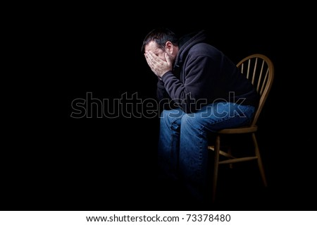 A depressed man sitting in a chair with his hands over his face, shot on black - stock photo