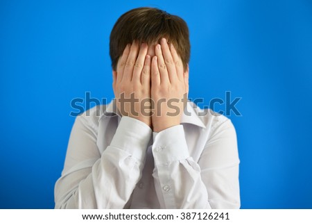 A depressed teenager boy covered his face with his hands - stock photo
