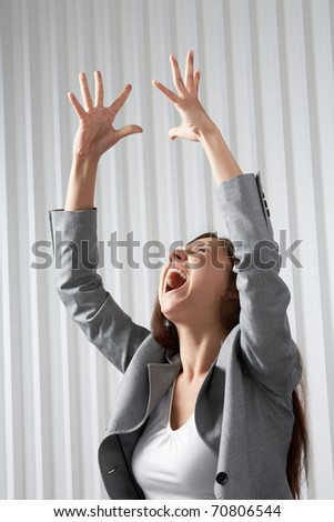 A depressed woman raising her hands and screaming - stock photo