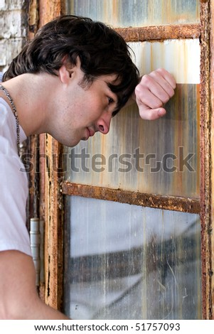 A depressed young model posing in a grungy urban setting. - stock photo