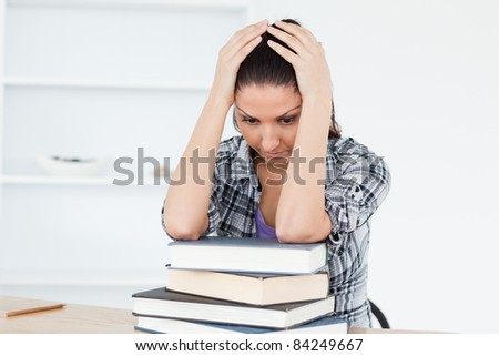 A depressed young student is leaning on books