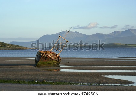 A derelict fishing boat at Ettrick Bay, Bute, with the island of Arran in the background - stock photo