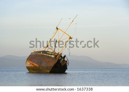 A derelict fishing boat lit by morning sunshine off the coast of Bute - stock photo