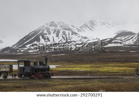 A derelict industrial train in Ny Alesund, Spitzbergen on a gloomy day - stock photo
