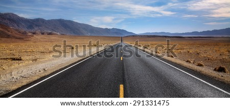 A Desert Highway And Distant Mountains In Death Valley National Park, California, USA - stock photo