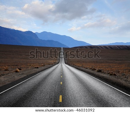 A Desert Highway Rolling Towards Distant Hazy Blue Mountains, Death Valley National Park, California - stock photo