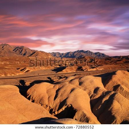 A Desert Highway Traversing The Bizarre Mars-Like Landscape Of Heavily Eroded Ridges At Zabriskie Point, Death Valley National Park, California, USA - stock photo
