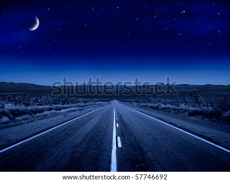 A desert road at night leading off into infinity. - stock photo