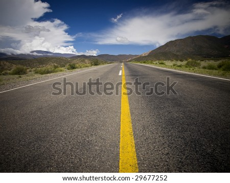 A desert road by the mountains surrounded by colorful nature. - stock photo