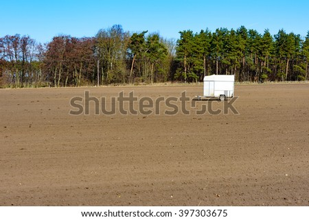 A deserted and abandoned horse trailer left on a harrowed farmers field in spring. Copy space in soil. Forest in background. - stock photo