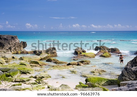 A deserted beach in Bermuda with deep blue sea, rocks and crashing waves