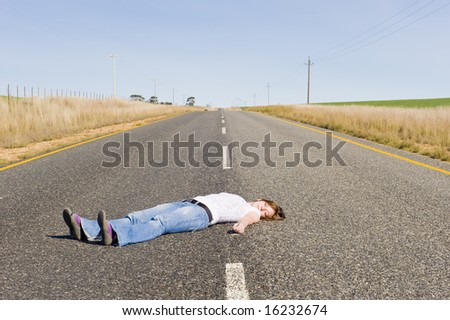 A deserted country road running through some green fields with a girl lying in the middle of the road playing dead. - stock photo