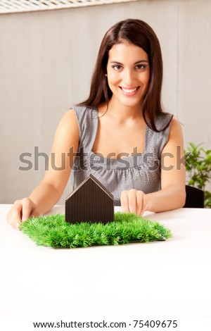 A design professional showing a green living concept - sharp focus on house - stock photo