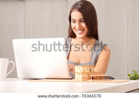 A designer or architect at desk with computer and model house - stock photo