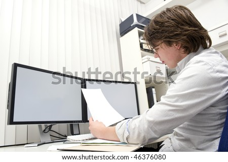 A designer, studying a ducument from the thick file in front of him behind his desk - stock photo
