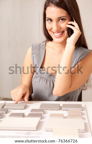 A designer talking on the phone choosing a stone tile - stock photo