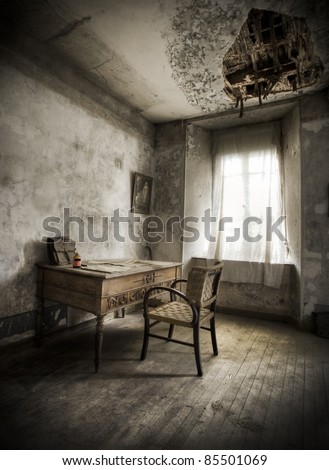 A desk in a creepy atmosphere, broken ceiling and moody light. - stock photo