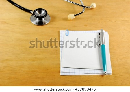 A desk top with stethoscope, notebook and pen - stock photo