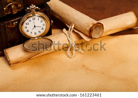 A desk with treasure box, old paper rolls and pocket watch with open lid.  - stock photo