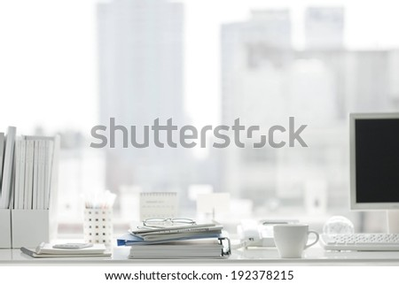 A desktop is full of various items and a computer. - stock photo
