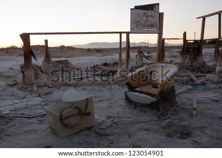 A desolate Salton Sea post-apocalyptic scene of a broken chair in front of a TV in a desert. - stock photo