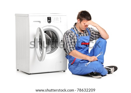 A desperate repairman posing next to a washing machine isolated on white background - stock photo