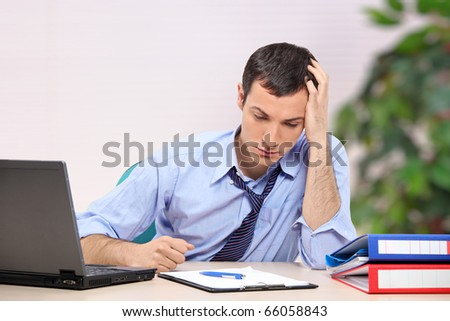 A desperate young businessman in the office looking down - stock photo