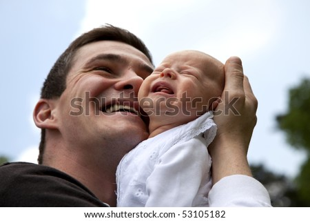 a desperate young father trying to calm down his crying 7 weeks old daughter without success