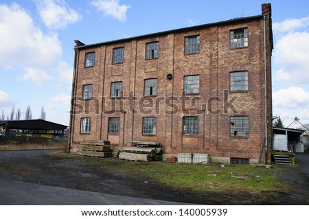 A detached industrial ruin with broken windows - stock photo