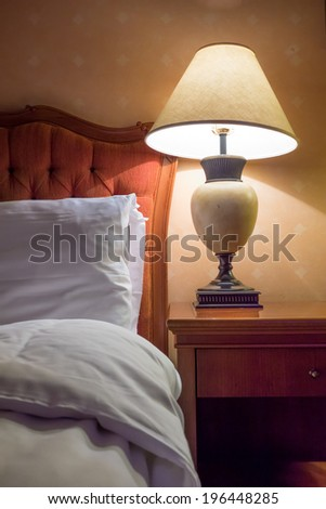 A detail from a hotel room with warm lighting as vertical composition
