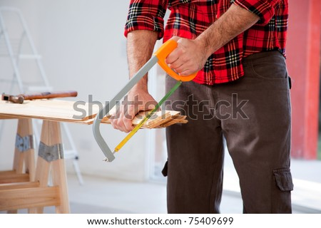 A detail of a man cutting wood with a small hand saw - stock photo