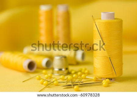 A detail of a sewing kit with cottons, pins and thimble on yellow background. - stock photo