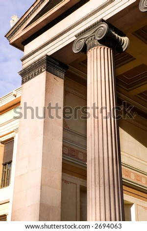 A detail of an old building built in the old Greek style with Ionic columns.