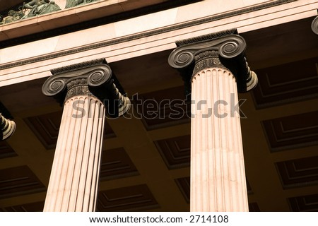A detail of an old building built in the old Greek style with Ionic columns. - stock photo
