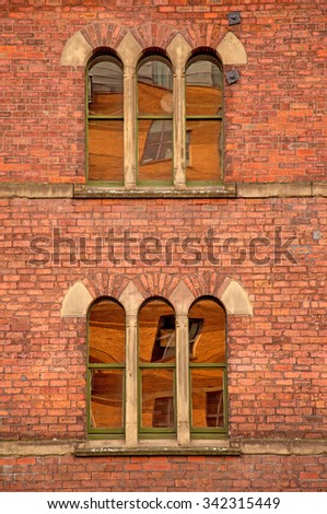 A detail of arched windows picked out in sandstone as part of a Victorian warehouse - stock photo