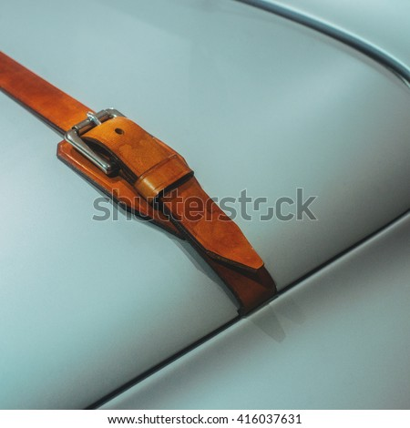 A detail of metallic grey car hood element with leather strap.  - stock photo