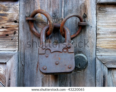 a detail shot of an old door and rusty lock