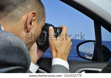 a detective or a paparazzi taking photos from inside a car - stock photo