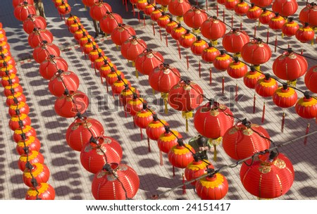 A devotee prays under hundreds of red lanterns at Thean Hou temple, Kuala Lumpur, Malaysia. - stock photo