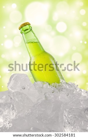 A dewy bottle with full of beer in cold ice cube, shot with bokeh background - stock photo