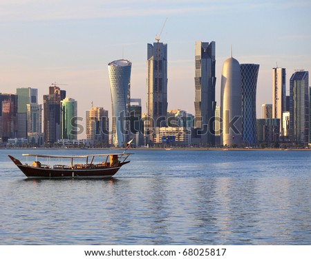 A dhow returns to harbour in Doha, Qatar, at sunset, with the city's modern skyline in the background. - stock photo