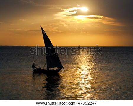 A dhow sailing boat in the sunset in Zanzibar - stock photo