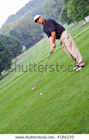 A diagonal photo of a golfer - room for text. - stock photo