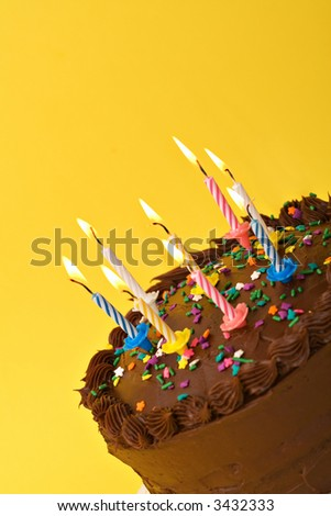 A diagonal shot of birthday or anniversary cake with lit candles. - stock photo