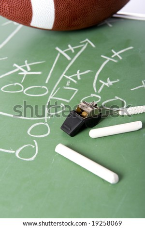 A diagram of a football play on a chalkboard with a football, chalk, eraser ane a whistle - stock photo